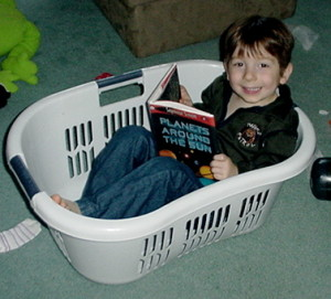 One of my twins around the age of 4 happily reading about the Solar System in a laundry basket.